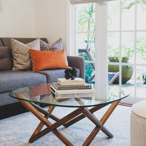 Living Room in Coconut Grove with warm and inviting colors that showcase a dark gray sectional and comfortable ottomans