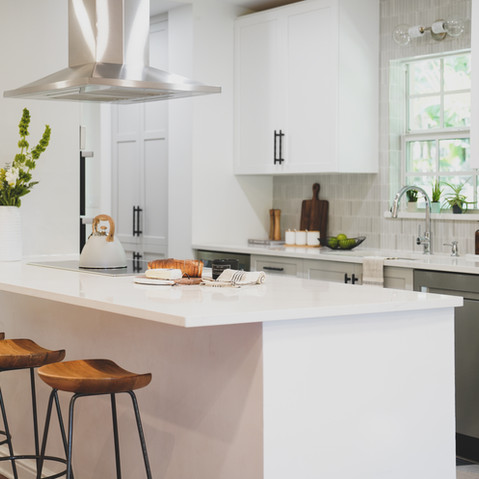 Bright, white and airy galley kitchen in Coconut Grove, Florida that features a Ann Sacks backsplash and a bold geometric flooring.