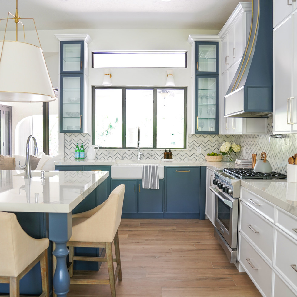 Large transitional modern kitchen with white cabinets and blue island