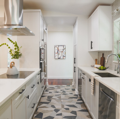 Modern Galley kithchen featuring white and gray cabinets.
