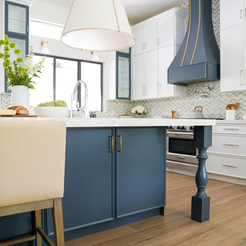 Transitional white kitchen with custom blue island