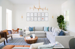 Modern transitional living room with gallery wall and blue accents