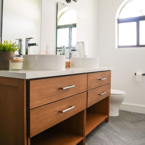 Modern bathroom with teak vanity with black accents and slate concrete tile