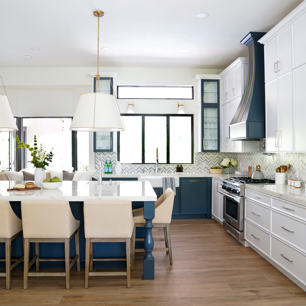 Large modern kitchen with white cabinets and blue island