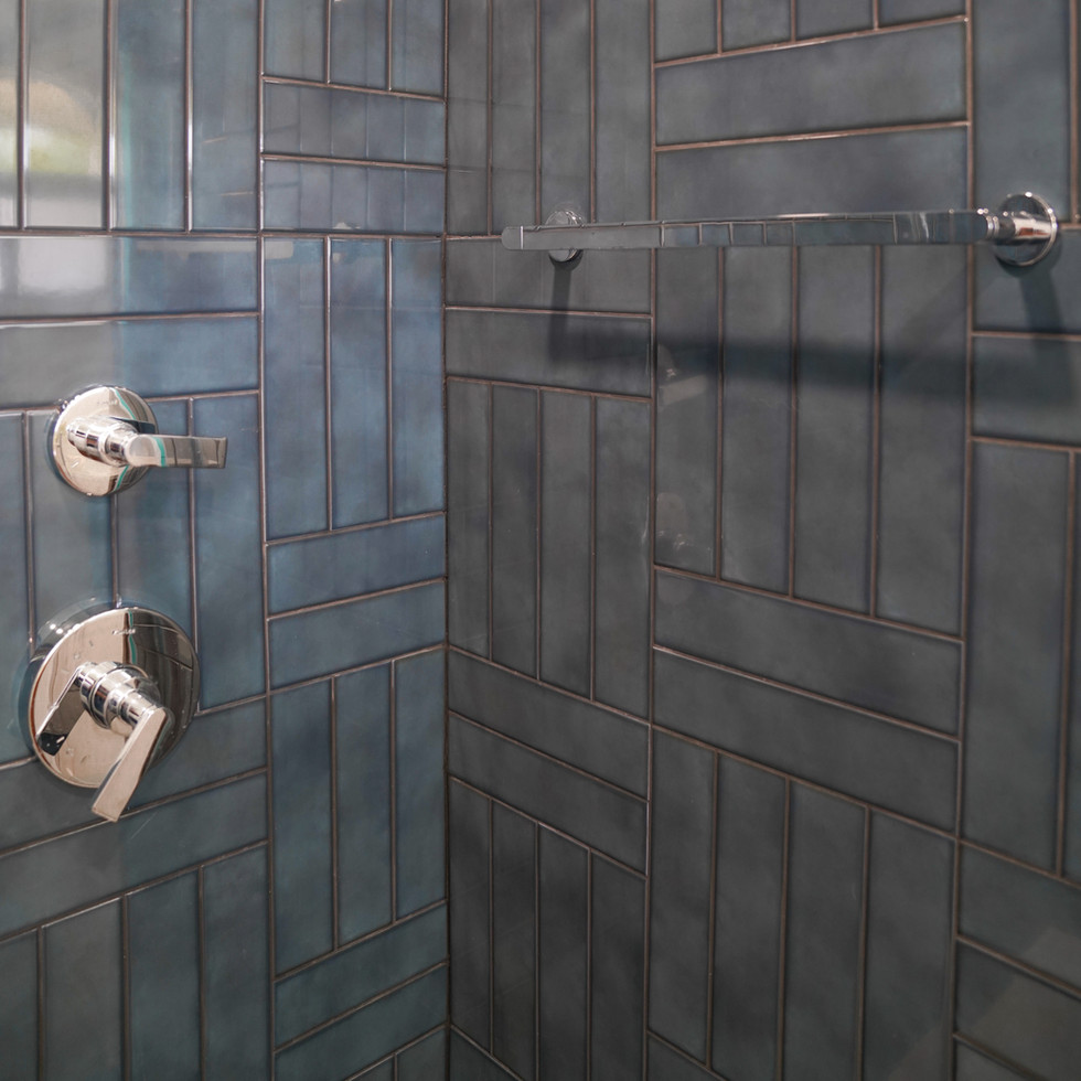 Modern bathroom with blue subway tile in shower