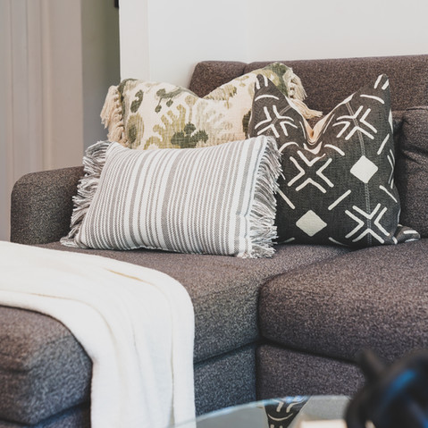 Living Room in Coconut Grove with warm and inviting colors that showcase a dark gray sectional and bold accent pillows