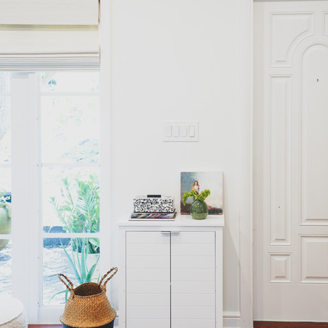 White entry cabinet that holds shoes