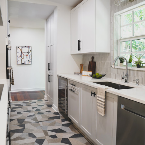 Bright, white and airy galley kitchen in Coconut Grove, Florida that features a Ann Sacks backsplash