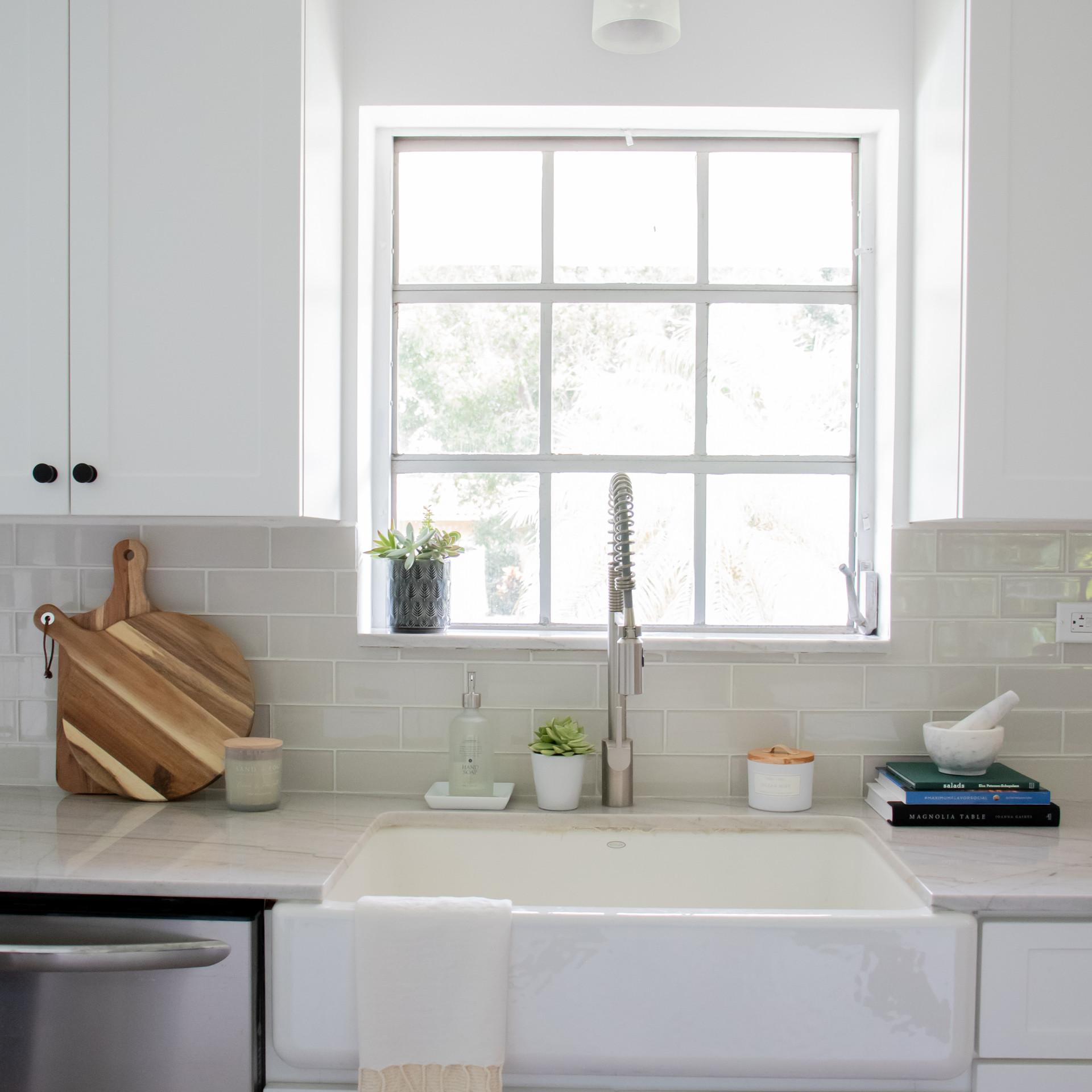 Modern bright white galley style kitchen with farm house sink designed by Miami based interior design studio KJ Design Collective