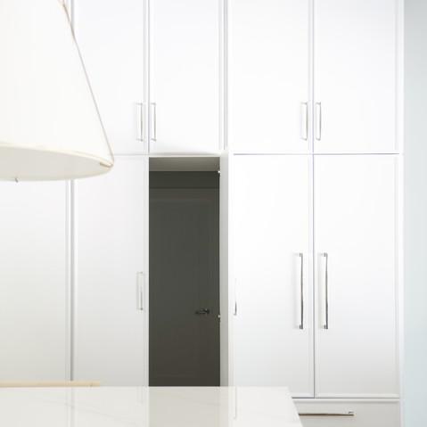 Transitional white kitchen with custom hidden door