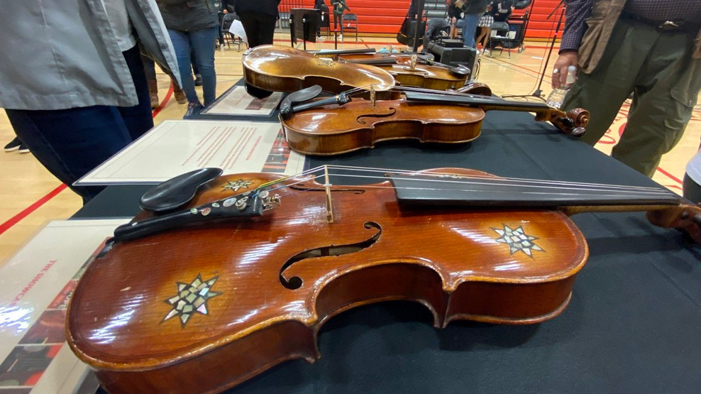 Event attendees view violins that belonged to Jews before and during the Holocaust. All violins now belong to a private collection owned by violin makers Amnon and Avshalom Weinstein.