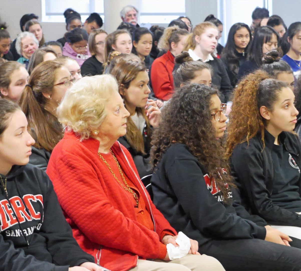 Helen Farkas, front and center, sits with Mercy High School students while listening to a guest speaker.