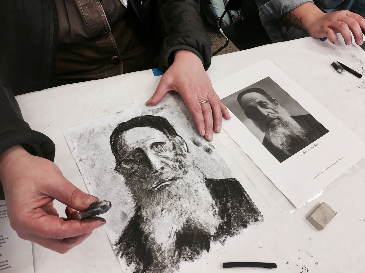 A Woodside Priory student creates a vivid charcoal drawing depicting Holocaust Survivor Pinchas Schumacher.