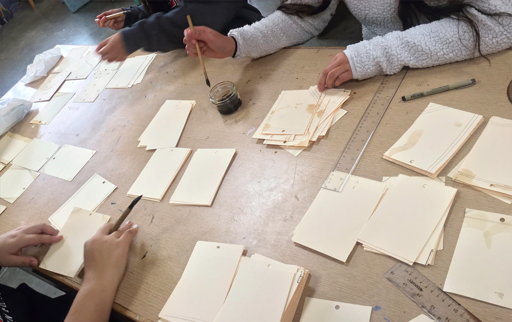 Student artists use house-made walnut ink to create luggage labels with a vintage feel as part of the suitcase installation project.