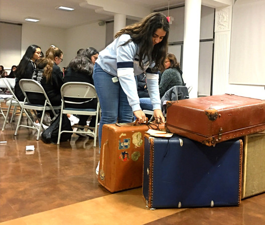 In the suitcase installation project at the Kristallnacht 2019 event, a student places a suitcase from her group with the other suitcases. The suitcases were picked up and moved throughout campus in the following weeks by different classes and student groups, and made guest appearances at many Mercy High School events including the fall play theater lobby, cafeteria, library, and various locations in the school hallways, courtyards and gardens.