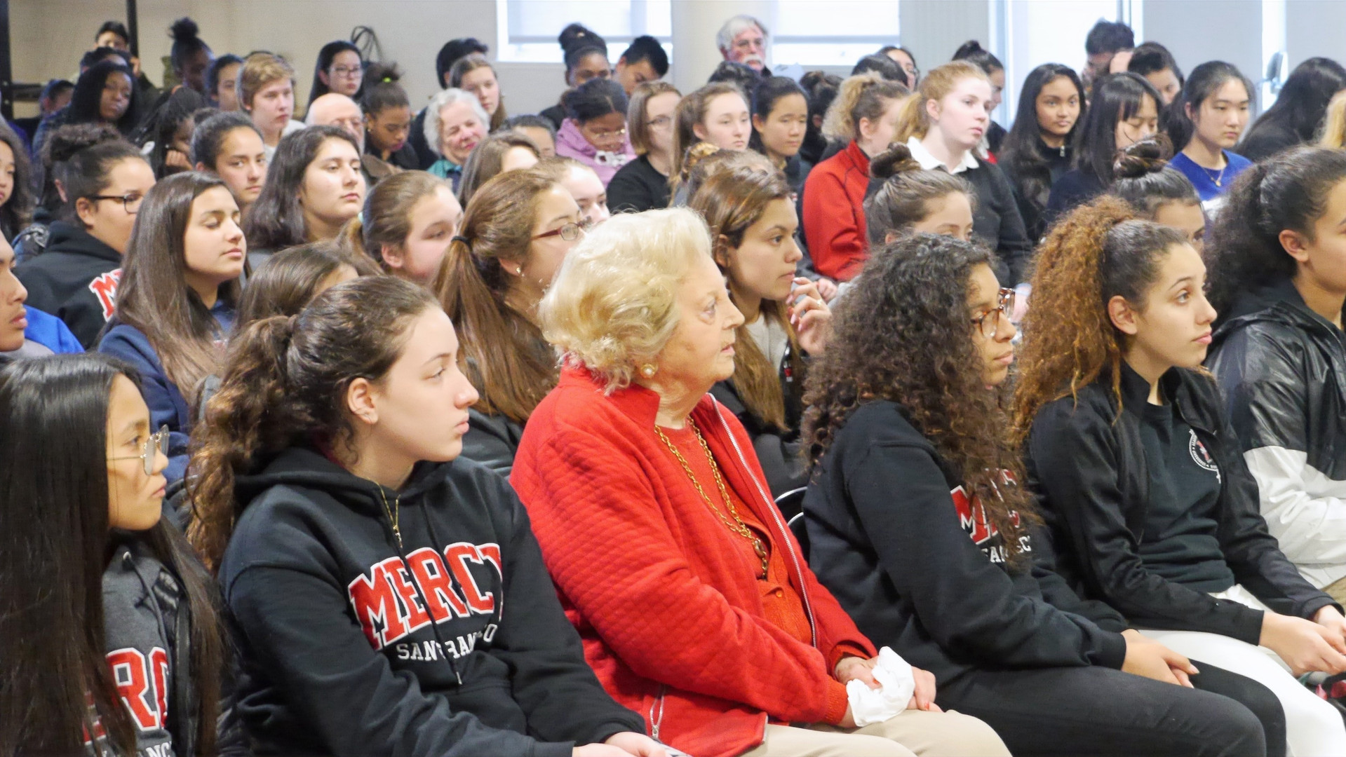 Survivor Helen Farkas (front and center) listens to a guest speaker with Mercy High School students.