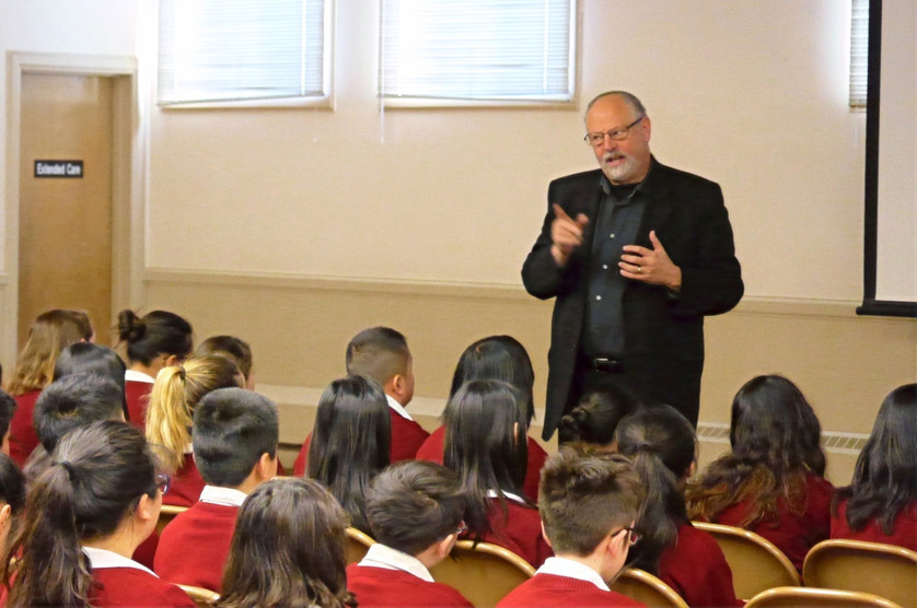 """Rabbi Peretz Wolf-Prusan speaks with St. Cecilia School students at the """"Voices of the Generations"""" Holocaust Remembrance Day event."""