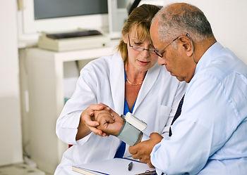 Woman taking man's blood pressure
