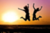 Two-Girls-Silhouette-Jumping-on-the-Beac