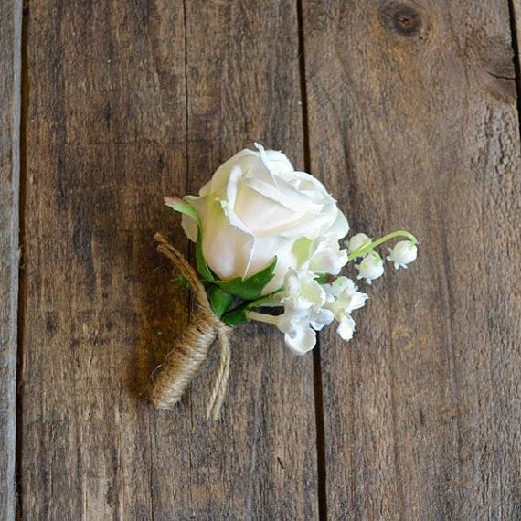 La boutonnière du marié : une rose blanche et un brin de muguet