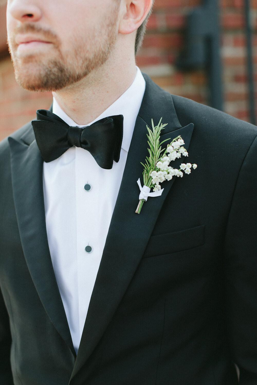 La boutonnière du marié : un brin de muguet et du sapin