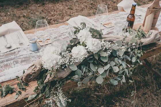 Décoration de table d'un mariage champêtre en extérieur en Espagne avec un centre de table en bois flotté
