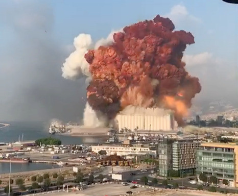 Huge explosion rising from silo building with white cloud and large orange cloud extending high up in the sky.