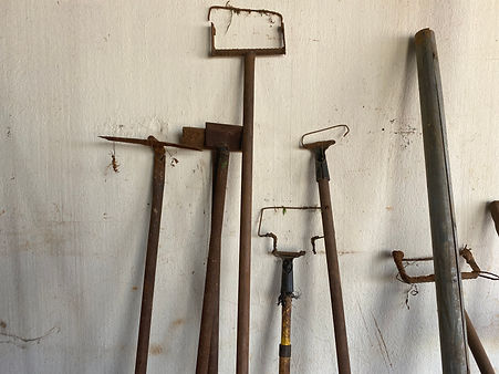 The Green Van handmade weeding tools leaning against a wall.