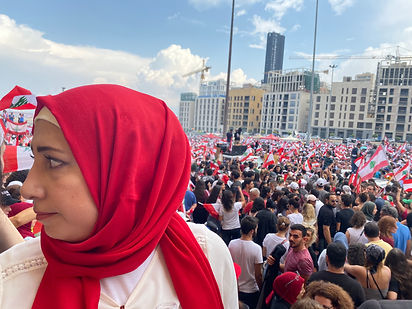 Face of woman with red scarf against backdrop of demonstration crowds in Beirut, during October 2019 Revolution.