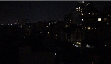 Night shot of Beirut during power outage, with few building lights.