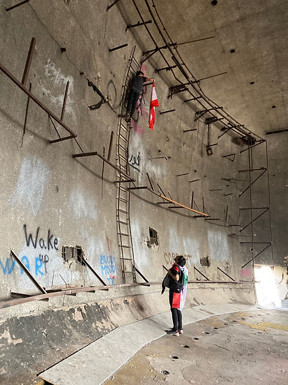 A man standing high on wall ladder inside an abandoned building, hanging a Lebanese flag while his friend below looks up.