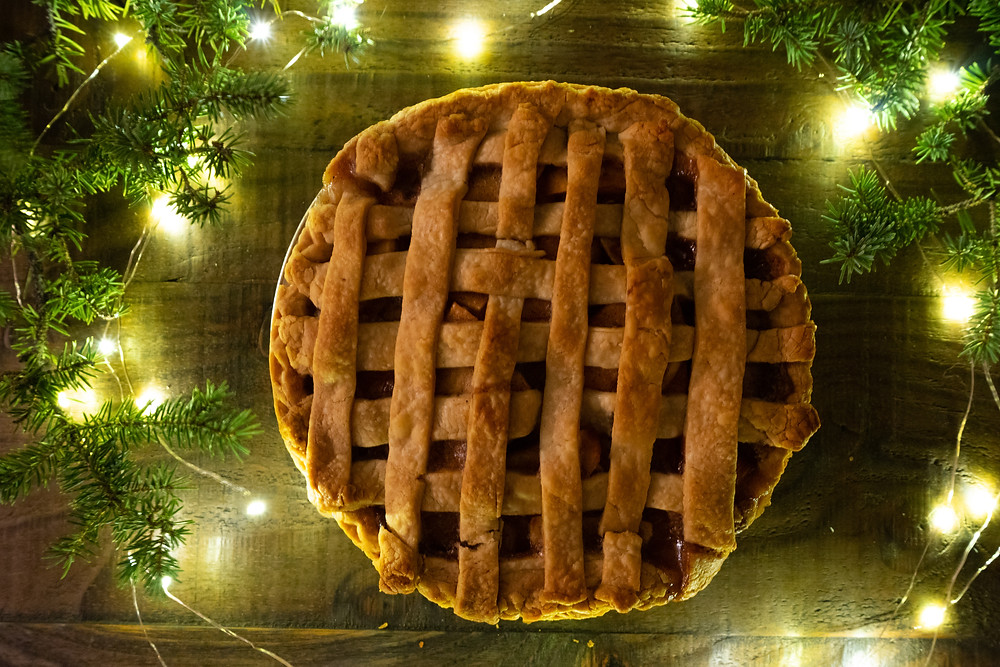 apple pie filling with apples, cinnamon, nutmeg, and allspice and lattice crust surrounded by fairy lights and Christmas tree branches sitting on wood table