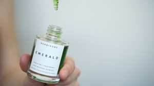 Emerald CBD oil by Herbivore, a green facial oil against a white wall