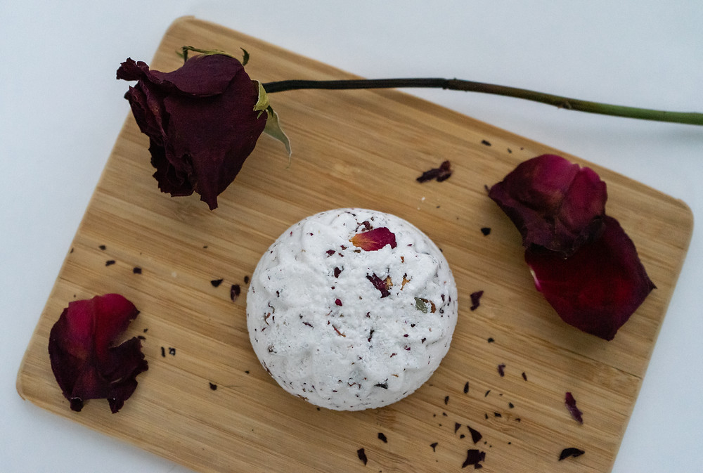 flatlay of rose bud and geranium bath bomb with dried rose petals, a dried rose, and crumbled roses on a cutting board on a all white background