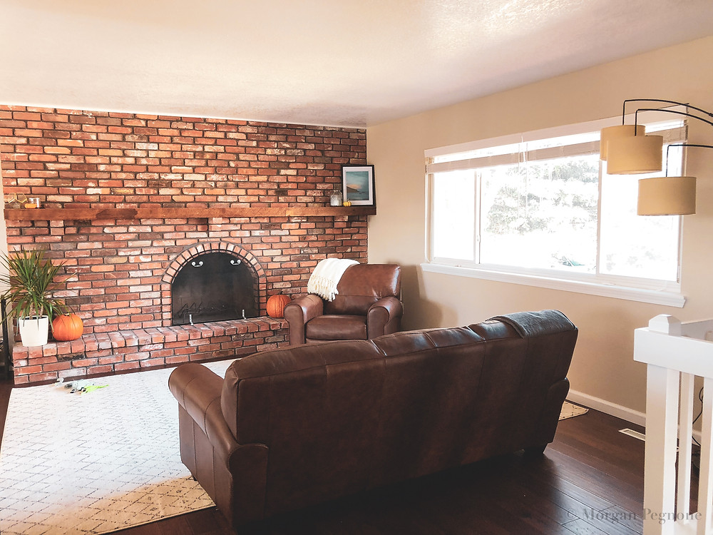 living room with brick fireplace and leather sofas