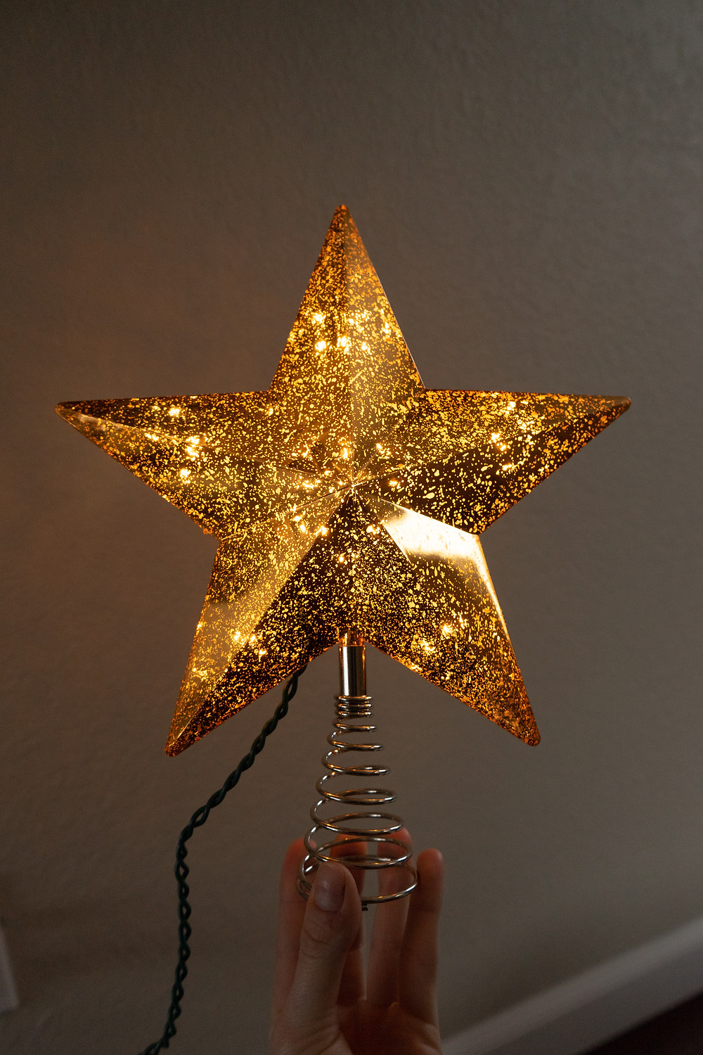 Holding a gold mercury star tree topper for christmas