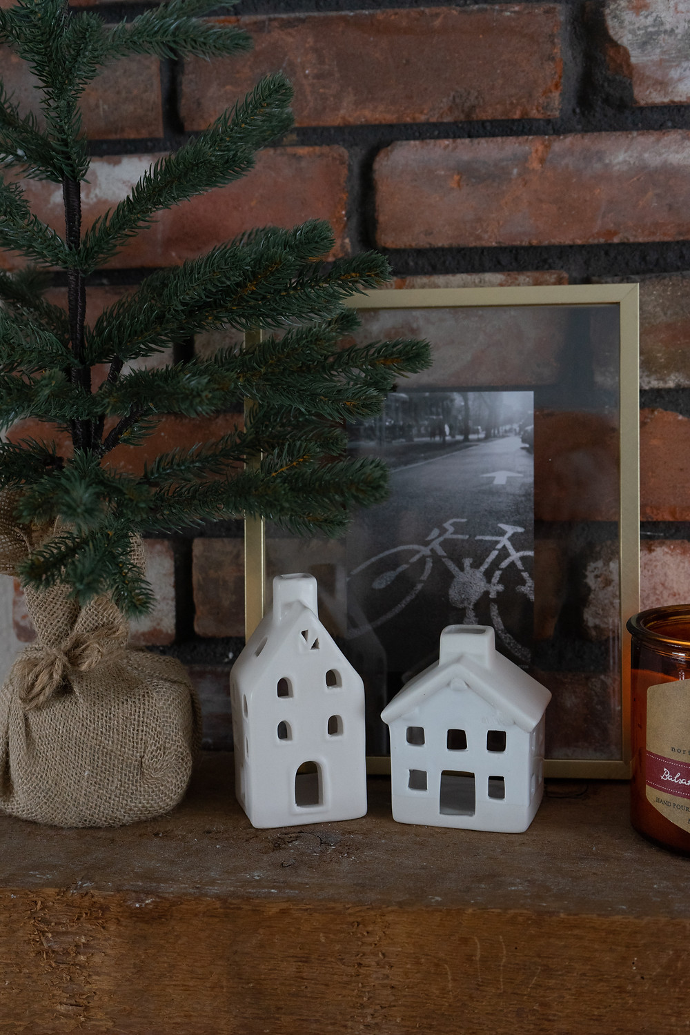 Faux tree in burlap next to two white ceramic homes with a gold picture frame behind. A glowing candle is on the right and the decor is sitting on a wooden mantel on a brick fireplace