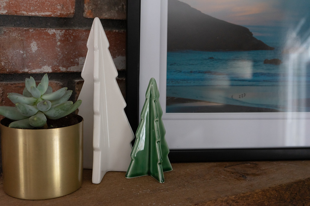 large white and small green ceramic trees next to a green succulent in a gold pot and a picture frame of the beach