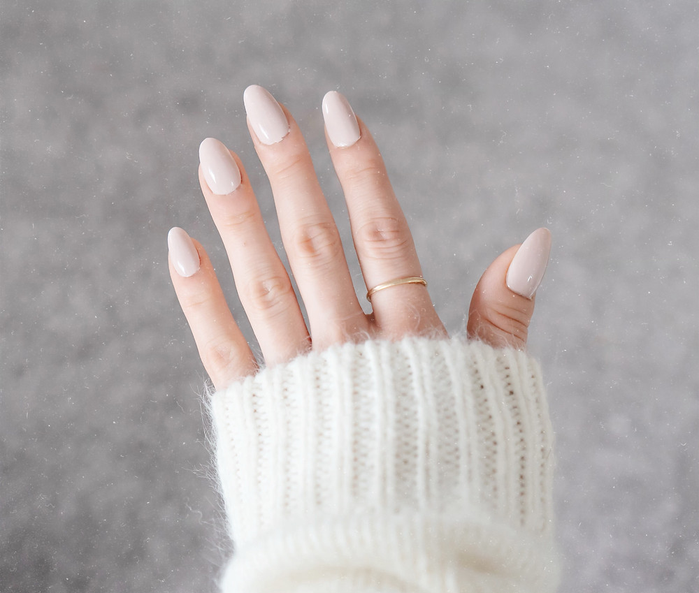 nailbliss press-on acrylic nails in almond against a grey carpet and morgan is wearing a white kit sweater