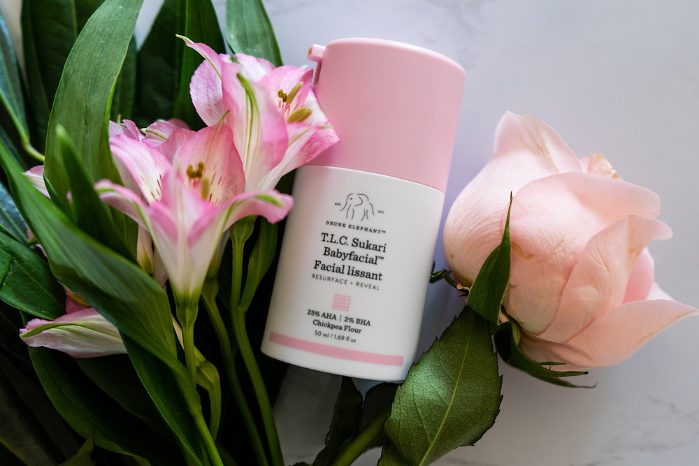 drunk elephant skincare TLC sukari babyfacial weekly resurfacing at-home facial treaetment with pink flowers and roses on a marble background