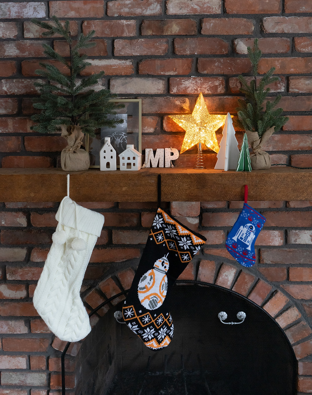 Christmas mantel with two faux trees in burlap, white ceramic houses, gold mercury star tree topper, gold picture frame, M and P white and gold dotted ornaments with a white and green ceramic tree. Hanging from the mantel is a white knit stocking, and two Star Wars stockings. All sitting on a red brick fireplace and wood mantel