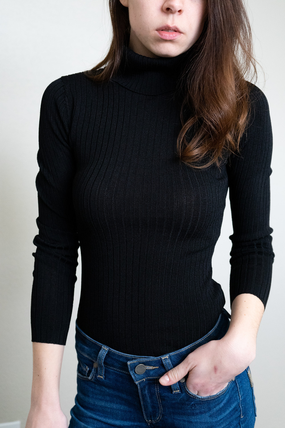 front view of wavy hair model wearing black ribbed zander turtleneck by babaton at aritzia with medium colored paige jeans