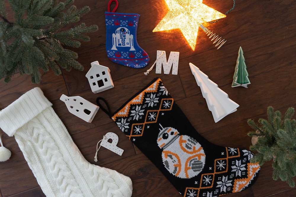 flat of Christmas decor items such as white knit stocking, Star Wars stockings, two faux trees in burlap, M & P white with gold dot ornaments, two ceramic trees and a gold mercury star tree topper on a dark hardwood floor