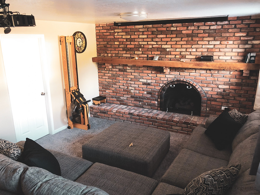 basement with brick gas fireplace with an L-shaped couch and projector