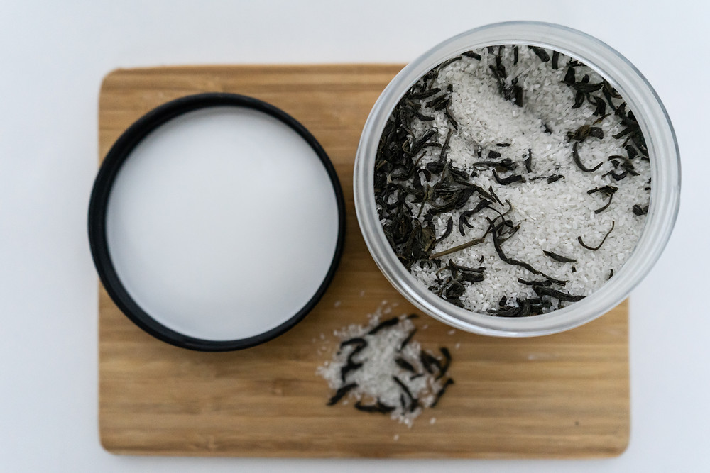 flatlay of jasmine clay detoxifying bath salts sitting on a cutting board with a tablespoon of bath salts sitting next to container - cutting board is sitting on all white surface