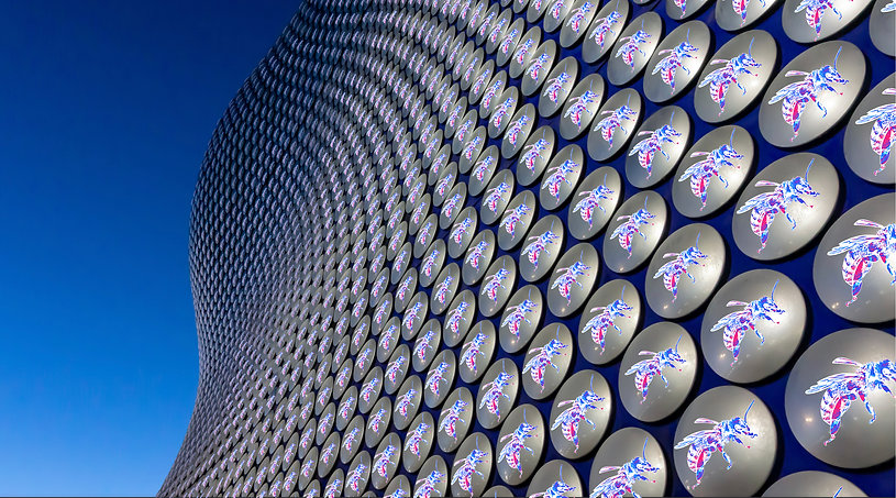 The iconic Selfridges building in Birmingham uk. Stephen Calcutt has placed a graffiti stencil of a bee on its silver discs as a tribute to the bees