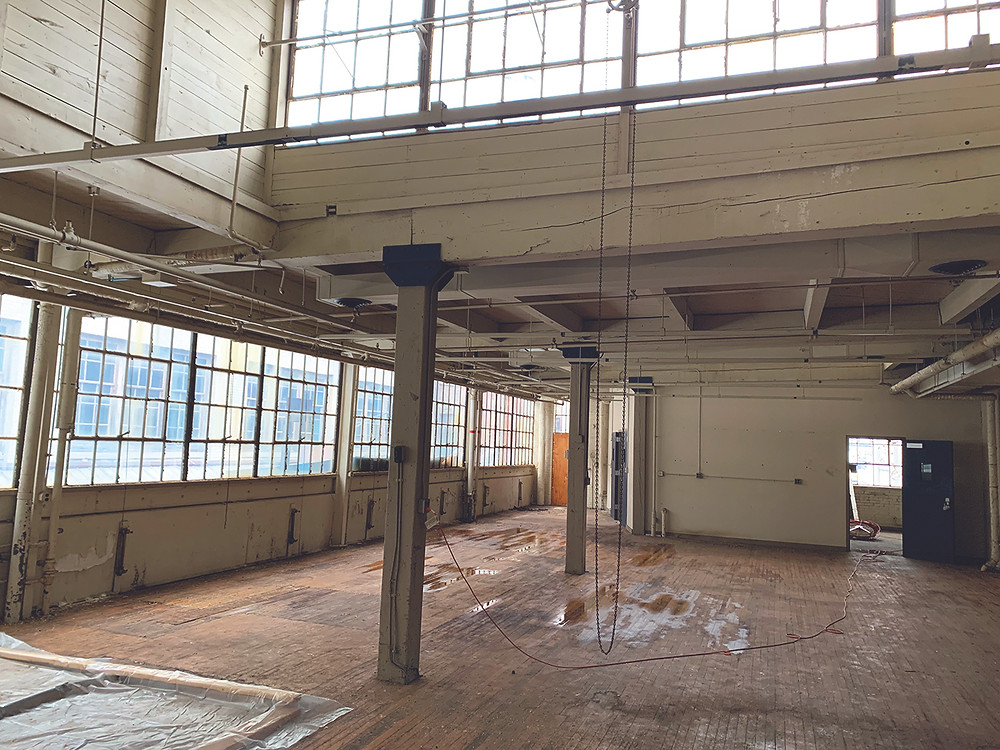 Factory loft interior with windows to be developed as Community within the Corridor in Milwaukee