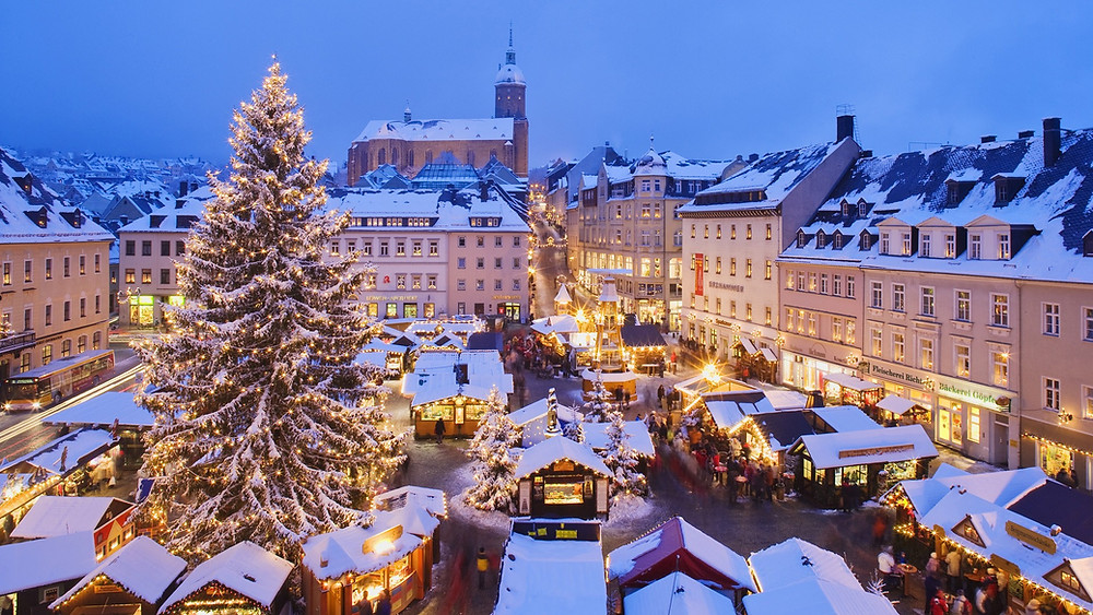 German market square with large Christmas tree in the snow