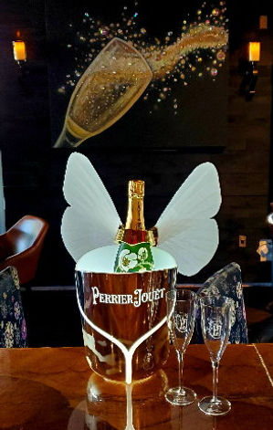 Perrier Jouet Champagne in wine bucket in front of champagne painting
