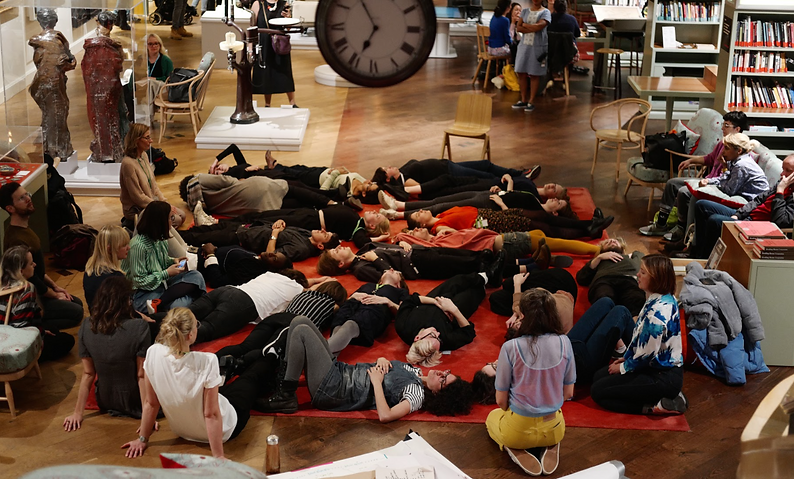 Wellcome Collection lie on a red carpet and sing